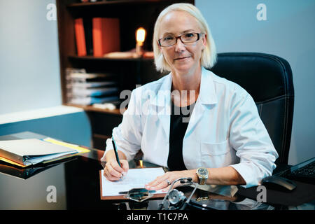 Portrait Of Female Doctor Working In Hospital Office Smiling At Camera - Stock Image