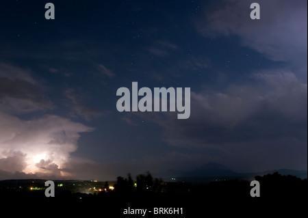 Night time lightning illuminating clouds - Stock Image