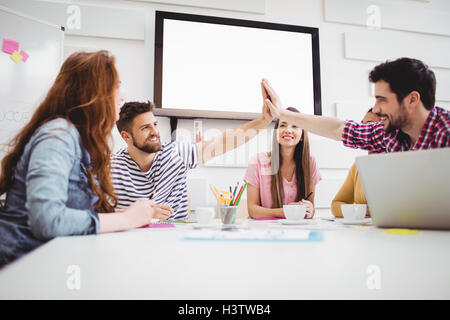 Male colleagues giving high-five in meeting at creative office - Stock Image