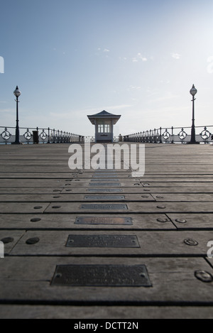 low angle view along the pier at Swanage towards some covered seating. The metal plates through centre image have - Stock Image