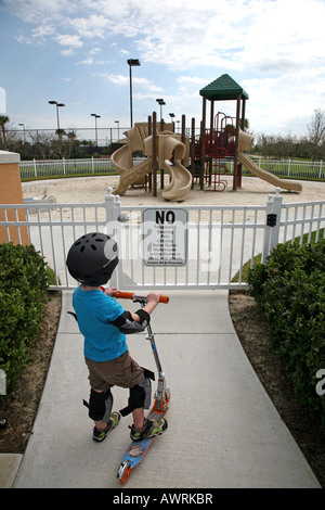 Boy on scooter staring at playground rules sign - Stock Image