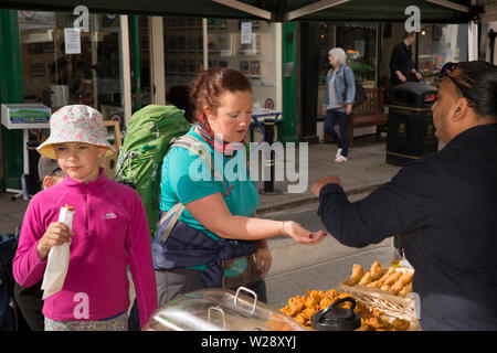 UK, Cumbria, Sedbergh, Main Street, monthly artizan's market, woman and child buying Indian takeaway food from roadside stall - Stock Image