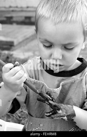 Blond haired toddler painting his own hand with a paint brush, in black and white. - Stock Image