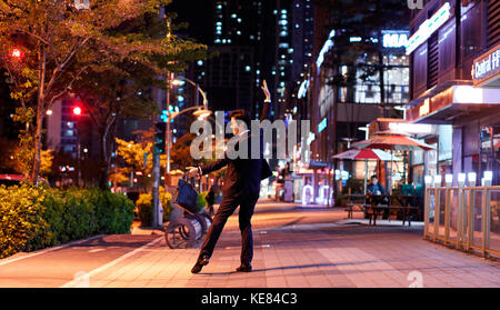 Businessman dancing on street in city at night - Stock Image
