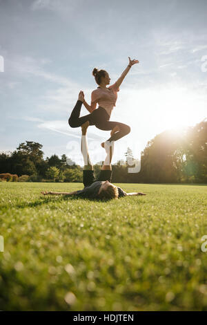 Vertical shot of healthy young couple doing acrobatic yoga on grass. Man and woman exercising in pair at the park. - Stock Image