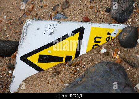 Danger warning sign half buried under sand. - Stock Image