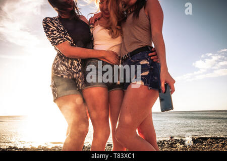 Group of young attractive woman i summer shorts stay together hugging with friendship outdoor with ocean and sunse tin background - youthful and peopl - Stock Image