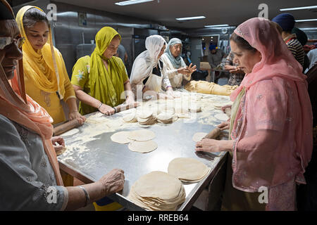 Women volunteers in a langar, a Sikh temple kitchen, prepare roti, a round thin bread. In South Richmond Hill, Queens, New York City. - Stock Image