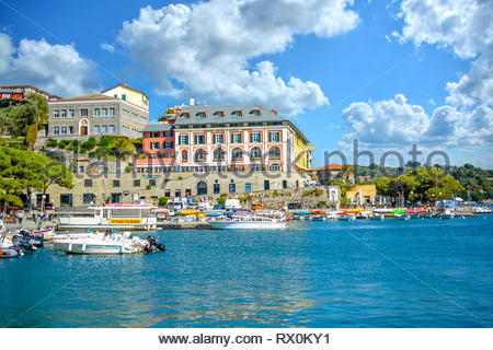 The colorful coastline of the resort city of Porto Venere, Italy, filled with tour boats on the Ligurian Sea in the harbor of the Gulf of Poets. - Stock Image