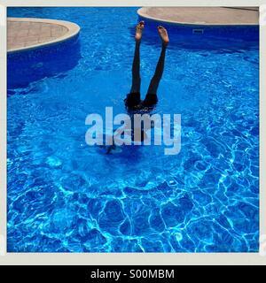 Teenage boy playing in swimming pool. - Stock Image