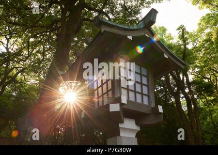 Sun burst behind traditional Japanese lantern near Meji Jingu Temple, Yoyogi Park, Tokyo, Japan. - Stock Image
