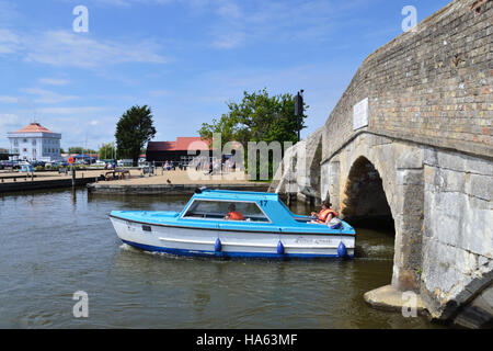 Day boat on the River Thurne navigating Potter Heigham Bridge on the Norfolk Broads. Herbert Woods tower and staithe - Stock Image