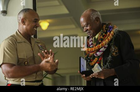 U.S. Marine Brig. Gen. Brian W. Cavanaugh, deputy commander of U.S. Marine Corps Forces, Pacific, presents the Congressional Gold Medal to Dr. Ernest James Harris, Jr. during a ceremony in Honolulu Nov. 12, 2016. Harris was awarded his Congressional Gold Medal for his service as a Montford Point Marine. - Stock Image
