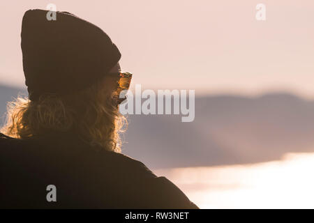 A man with long curly blond hair and wearing a beanie and sunglass looking out to sea. - Stock Image