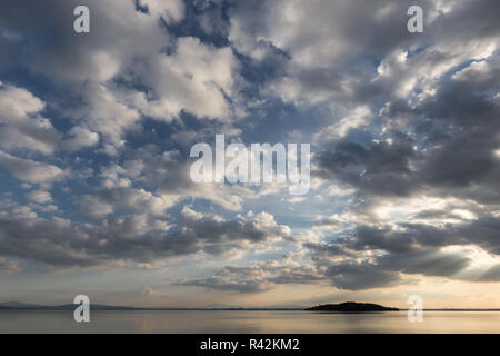 Trasimeno lake (Umbria, Italy) with big clouds at sunset above an island and blue sky. - Stock Image