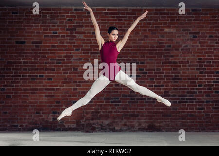 Graceful ballerina in red bodysuit jumping in the air. full length photo - Stock Image