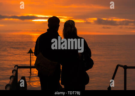 Aberystwyth Wales UK, Monday 17 June 2019  UK Weather:After day of showery rain and grey overcast skies, a couple are silhouetted as they watch the fiery sunset filling the sky over Cardigan Bay at Aberystwyth on the west wales coast.  photo credit: Keith Morris//Alamy Live News - Stock Image