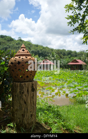 Ornamental Thai lantern on the bank of a lake with traditional dwellings in the background set against a dramatic cloudy sky. - Stock Image