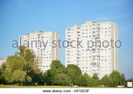 Two high apartment blocks and trees on the Orla Bialego area in Poznan, Poland - Stock Image