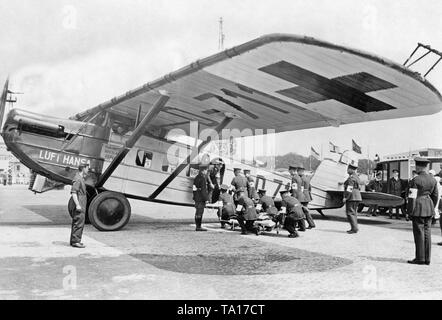 A Dornier Merkuer of the German Lufthansa during a loading exercise at the Berlin Tempelhof Airport. A patient on a stretcher is being loaded  into the plane  by Red Cross staff. - Stock Image