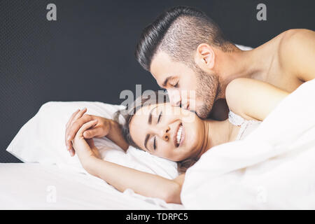 Happy couple waking up in the morning at home - Young lover having a tender moment boyfriend kissing his girlfriend in bed - Stock Image