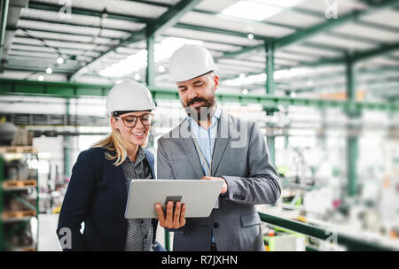 A portrait of a mature industrial man and woman engineer with tablet in a factory, working. - Stock Image