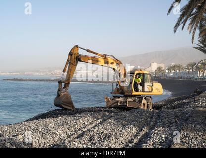 Hyundai R 170 W wheeled excavator maintaining sea defences in Costa Adeje, Tenerife, Canary Islands. - Stock Image