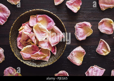 Brass Bowl of Dried Pink Rose Petals on Wood Table - Stock Image
