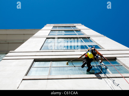 A window cleaner abseils down the facade of a high rise building in Lisbon, Portugal while cleaning office windows - Stock Image