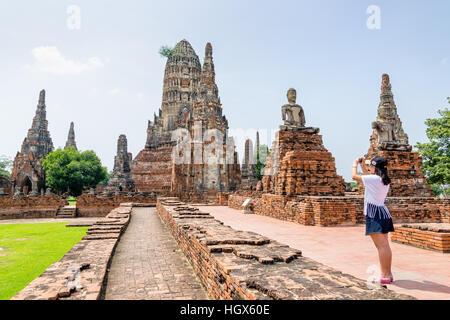 Tourist teenage girl take a photo ancient pagoda of Wat Chaiwatthanaram is buddhist temple famous tourist attraction - Stock Image