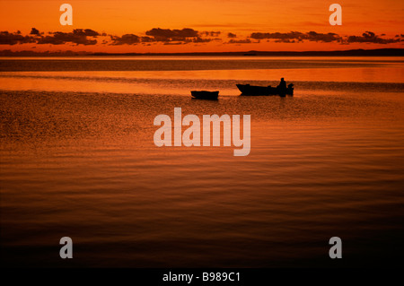 Man in dinghy at sunrise - Stock Image