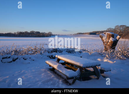 Outdoor table and bench set in the snow on a sunny early winter morning - Stock Image