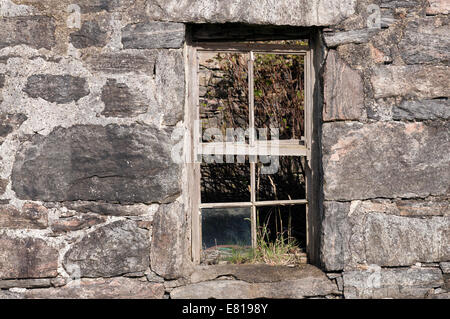 Old and broken sash window in a stone built derelict croft house in the Isle of Lewis. - Stock Image