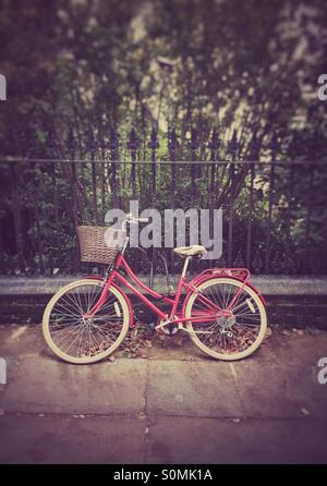 Red bicycle against a railing in Cambridge, UK. Retro/aged - Stock Image