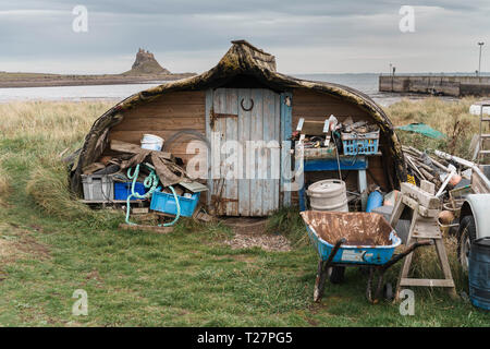 Lindisfarne or Holy Island, Northumberland coast south of Berwick-on-Tweed, England. The old fishing boats made into sheds, upside down. - Stock Image