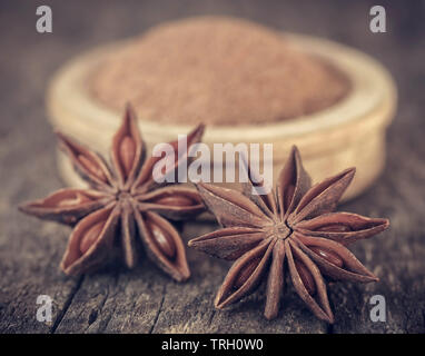 Whole and ground aromatic star anise on wooden surface - Stock Image