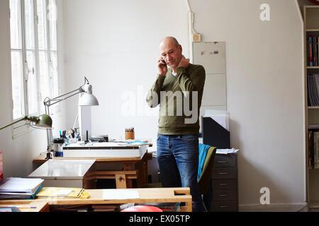 Mature man on the phone in creative studio - Stock Image