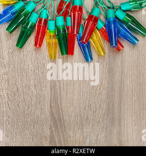 Christmas colorful lights on brown wooden background - Stock Image