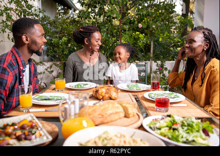 An African family sitting around a table for lunch - Stock Image
