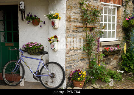 Stone house with streetside garden and bicycle at front door Holy Island of Lindisfarne Northumberland England UK - Stock Image