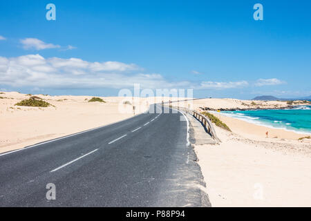 Curvy road through the dunes of Corralejo, Fuerteventura, in the Canary Islands, Spain. - Stock Image