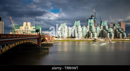 London, England, UK - May 28, 2019: The River Thames flows under Vauxhall Bridge, with the distinctive St George's Wharf apartment buildings behind. - Stock Image