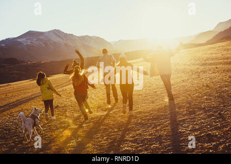 Big group of happy friends run and jump at sunset field against mountains and sun - Stock Image