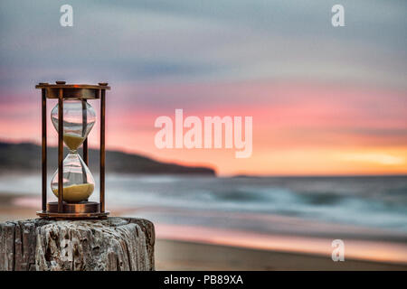 Hourglass outdoors standing on jetty post with moody sunrise sky. - Stock Image