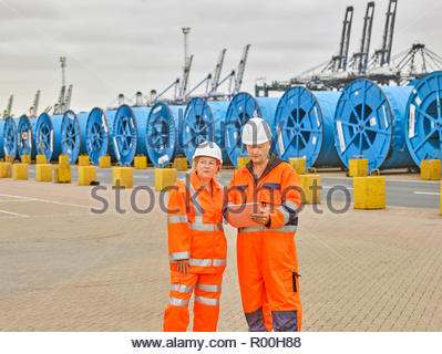 Dock managers talking on digital tablet to office in port moving freight - Stock Image