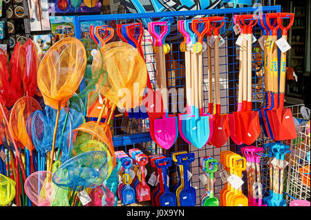 Colourful buckets and spades and fishing nets outside a shop front in Lyme Regis, Dorset - Stock Image