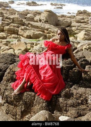 African Woman with Dreadlocks, Wearing a Red Dress, Sitting on Rocks by the Sea. - Stock Image