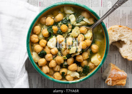 Chickpea soup with spinach and dry salted cod in a rustic bowl on a newspaper background - Stock Image