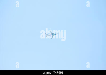 An airplane or a plane flies against a blue sky in a minimalist style. - Stock Image