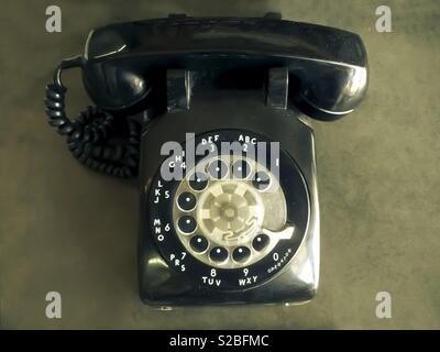 Old vintage rotary dial black telephone - Stock Image